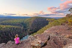 La femmina si siede la roccia con le viste sopra il fiume di Nepean e le montagne blu fotografie stock