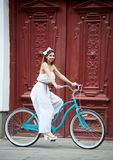 La femmina si siede sulla bicicletta contro sulla vecchia porta rossa del fondo fotografie stock libere da diritti