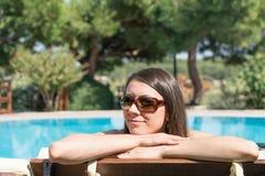 La femmina si siede vicino dalla piscina al ozcaada del recipiente del telefono di ora legale Fotografia Stock Libera da Diritti