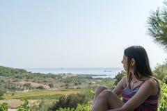 La femmina si siede vicino dalla valle al telefono Bozcaada Canakkale Turchia 2017 di ora legale Fotografie Stock