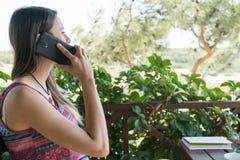 La femmina si siede vicino dallo stagno ad ora legale che mostra il gioco con il telefono cellulare astuto Bozcaada Canakkale Tur Immagini Stock