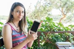 La femmina si siede vicino dallo stagno ad ora legale che mostra il gioco con il telefono cellulare astuto Bozcaada Canakkale Tur Fotografia Stock Libera da Diritti