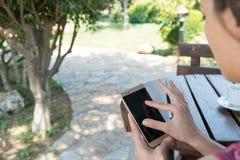 La femmina si siede vicino dallo stagno ad ora legale che mostra il gioco con il telefono cellulare astuto in Canakkale Turchia T Immagini Stock