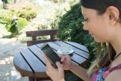La femmina si siede vicino dallo stagno ad ora legale che mostra il gioco con il telefono cellulare astuto in Canakkale Turchia T Fotografia Stock Libera da Diritti