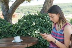 La femmina si siede vicino dallo stagno ad ora legale che mostra il gioco con il telefono cellulare astuto in Canakkale Turchia T Fotografia Stock