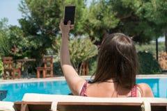 La femmina si siede vicino dallo stagno ad ora legale che mostra prendendo Selfie con il telefono cellulare astuto Bozcaada Canak Fotografie Stock Libere da Diritti