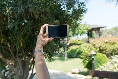 La femmina si siede vicino dallo stagno ad ora legale che mostra prendendo Selfie con il telefono cellulare astuto in Canakkale T Immagine Stock Libera da Diritti