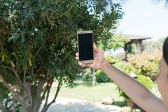 La femmina si siede vicino dallo stagno ad ora legale che mostra prendendo Selfie con il telefono cellulare astuto in Canakkale T Immagini Stock