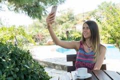 La femmina si siede vicino dallo stagno ad ora legale che prende il tè Canakkale del caffè della bevanda della foto di Selfie in  Immagine Stock