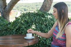 La femmina si siede vicino dallo stagno al tè Bozcaada Canakkale del caffè della bevanda di ora legale in Turchia 2017 Immagini Stock Libere da Diritti