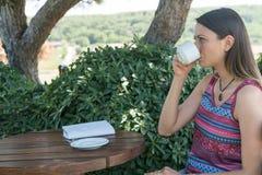 La femmina si siede vicino dallo stagno al tè Canakkale del caffè della bevanda di ora legale in Turchia 2017 Fotografia Stock