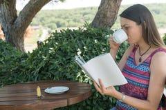 La femmina si siede vicino dallo stagno alla bevanda Coffe del libro di lettura di ora legale Fotografia Stock Libera da Diritti