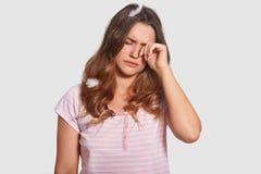 La femmina sonnolenta attraente sfrega gli occhi, odi si sveglia presto, ha piume sulla testa, vestita in pigiami, isolati sopra  fotografie stock libere da diritti