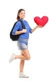 La femmina sorridente che tiene un cuore rosso ha modellato il cuscino Fotografia Stock