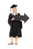 La femmina sorridente nella graduazione abbiglia la tenuta della freccia nera grande Immagini Stock