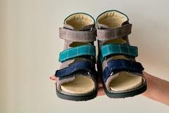 La femmina sta giudicando il primo piano sandali della scarpa ortopedica dei bambini speciali fatto di cuoio genuino fotografia stock