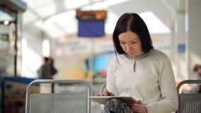 La femmina sta lavorando con il pc della compressa che aspetta nel corridoio dell'aeroporto stock footage