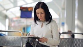 La femmina sta lavorando con il telefono che aspetta nella seduta del corridoio dell'aeroporto archivi video