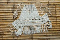 La femmina superiore ha tricottato il bianco, trovantesi su una tavola di bambù Foto per il catalogo Annata, hippy o hippy immagini stock