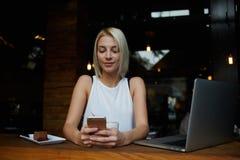La femmina sveglia ha letto il messaggio di testo sul suo Smart Phone mentre sedendosi nella caffetteria moderna con il computer  Immagini Stock Libere da Diritti