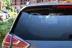 La fenêtre arrière d'une voiture a garé sur la rue dans le jour ensoleillé d'été, vue arrière Maquette pour l'autocollant ou les  photographie stock libre de droits