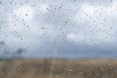 La fenêtre avec la pluie se laisse tomber sur le verre en dehors du paysage naturel Photos stock