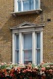 La fenêtre blanche sur le mur de briques est décorée des fleurs images stock