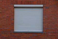 La fenêtre carrée s'est fermée par la jalousie grise sur un mur de briques Photos stock