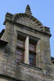 La fenêtre d'une maison en pierre située en Rocherfort-en-terre, France, est surmontée par un fronton incurvé sculpté Image libre de droits