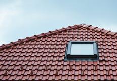 La fenêtre de lucarne de grenier sur les carreaux de céramique rouges logent le toit extérieur Les lucarnes de grenier autoguiden Photo libre de droits