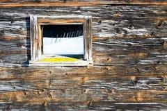 La fenêtre de vintage de la vieille carlingue en bois reflète le paysage d'hiver Fond rustique en bois Photographie stock libre de droits