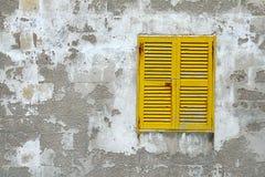 La fenêtre en bois jaune shutters sur le vieux mur en pierre Photos libres de droits