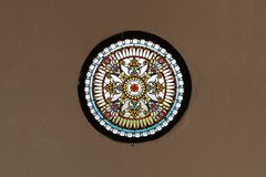 La fenêtre en verre teinté d'église, métaphorique, cercle colore le verre sur le papier peint brun concret Photo stock