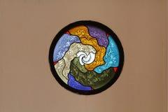 La fenêtre en verre teinté d'église, métaphorique, cercle colore le verre sur le papier peint brun concret Photographie stock