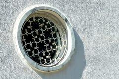 La fenêtre ronde avec la grille de fer travaillé photographie stock