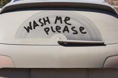 La fenêtre arrière sale de la voiture et l'inscription svp me lavent Image stock