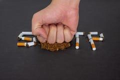 La fermata di parola che fuma su un fondo nero, ferma fumare e mani che stanno andando smettere di fumare immagini stock