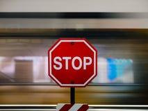 La fermata firma dentro il rosso contro il treno commovente confuso Fotografie Stock Libere da Diritti