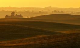 La ferme sur les champs onduleux de l'automne Image stock