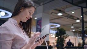 La ferretería, cliente de la mujer joven teléfono móvil moderno selecciona y de la prueba almacen de video