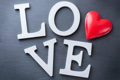 La festa del giorno di biglietti di S. Valentino segna il messaggio di testo con lettere per amare il fondo della carta Immagini Stock