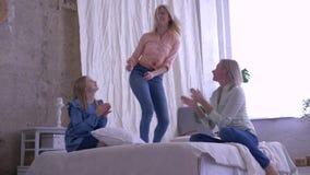 La festa di famiglia, figlie divertenti con la madre è divertentesi e cantante sul letto nella sala a casa