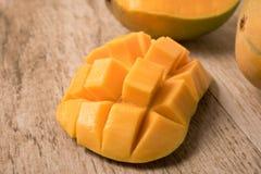 La fetta del mango ha tagliato ai cubi con il mango fresco sulla tavola di legno immagine stock libera da diritti