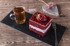 La fetta di dolce rosso del velluto con glassare bianco è guarnita con le fragole vicino su immagine stock libera da diritti