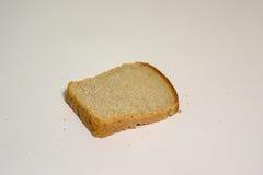 La fetta di pane con le briciole isotated su fondo grigio Immagine Stock