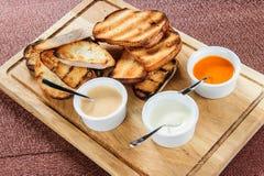 La fetta di pane tostato arrostita dentro impanata con formaggio e sesamo ha slittato con salsa su un bordo di legno Immagini Stock Libere da Diritti