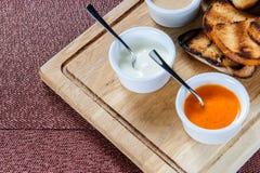 La fetta di pane tostato arrostita dentro impanata con formaggio e sesamo ha slittato con salsa su un bordo di legno fotografie stock libere da diritti