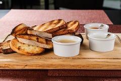 La fetta di pane tostato arrostita dentro impanata con formaggio e sesamo ha slittato con salsa su un bordo di legno fotografia stock
