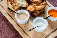 La fetta di pane tostato arrostita dentro impanata con formaggio e sesamo ha slittato con salsa su un bordo di legno immagine stock