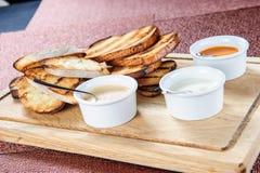 La fetta di pane tostato arrostita dentro impanata con formaggio e sesamo ha slittato con salsa su un bordo di legno fotografie stock